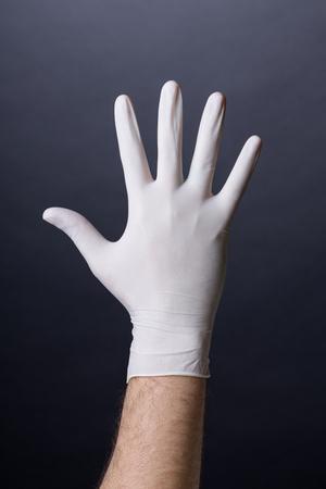 latex glove: Male palm in latex glove. Doctor or nurse hand in sanitary glove. Dark background