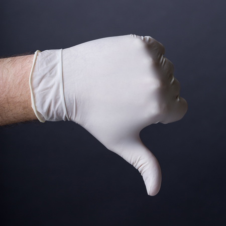 latex glove: Male hand in latex glove. Thumb down sign. Bad outcome, medical failure, bad healthcare concept. Dark background