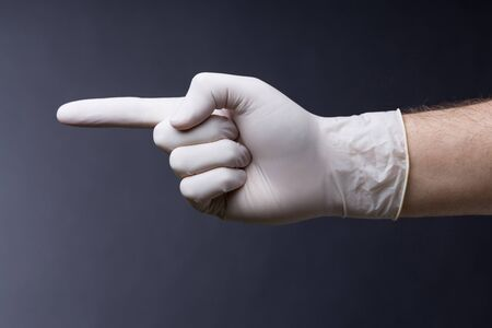 latex glove: Male hand in latex glove. Doctor or nurse poiting with a finger. Dark background