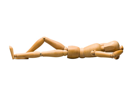 Wooden mannequin lying down, isolated on white. Stock Photo
