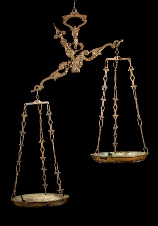 unfair: Antique weighing scale on black background. Justice, making decisions, true and false, fair and unfair concept.