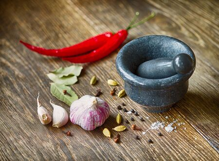 ingridients: Spices in wooden bowls and mortar with pestle. Cooking ingridients, gourmet kitchen, eastern spices concept.