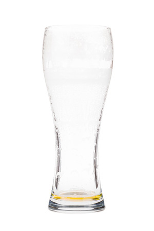 pewter mug: Almost empty beer glass. Light lager beer remains in a tall glass. Isolated on white background Stock Photo
