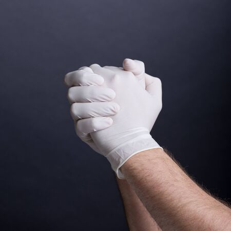 latex gloves: Male hands in latex gloves on dark background Stock Photo