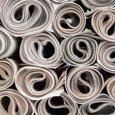 Stack of newspapers rolls, paper texture background. Banque d'images