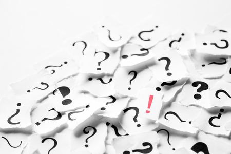 Pile of question mark signs scattered around with one red exclamation symbol in the center. Decision, enquiry or faq concept. Stock Photo