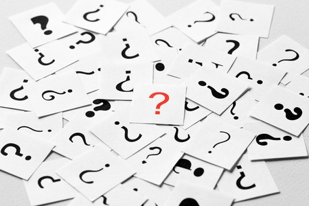 Pile of question mark signs scattered around with one red symbol in the center. Decision, enquiry or faq concept.