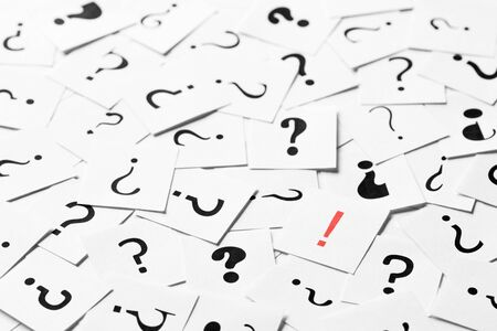 Pile of question mark signs scattered around with one red exclamation symbol in the center. Decision, enquiry or faq concept. Reklamní fotografie