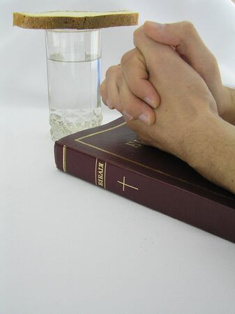 On a photo on a white background a glass with water, and bread, the Bible and hands combined in a pray. The photo is made in Ukraine. A symbol of gratitude to the God for I peep.