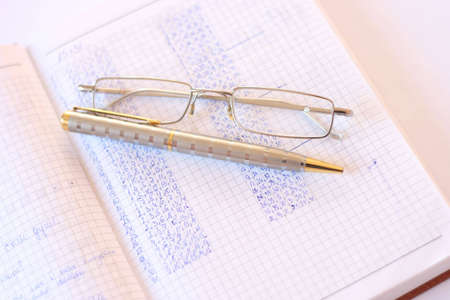 A silver pen, eyeglasses, and  notebook. photo