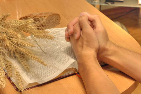 ON table Bible, the ear of the wheat and bread and hands of the person who be prayed