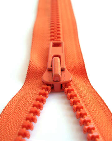 a orange zipper opened to a white surface                        Stock Photo