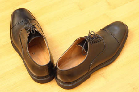 wearing sandals: black male loafers on yellow floor Stock Photo