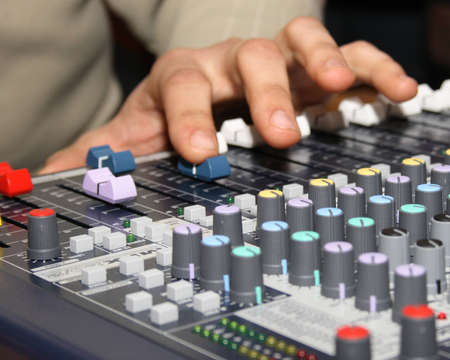 Sound engineer at mixing desk, daylight concert shot
