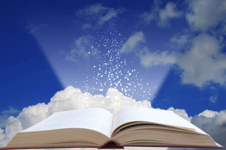 light from a book on a background sky and clouds