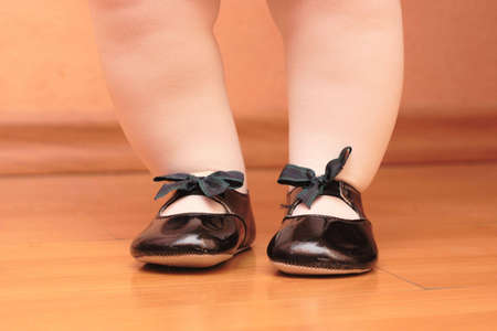 the feet of child are put on shoes in a shoe Stock Photo