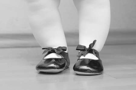 the feet of child are put on shoes in a shoe photo