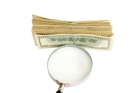 on photo magnifying glass and heap of the dollar bills on white background photo