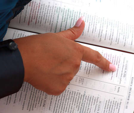 a hand with finger pointing a phrase on an old bible Stock Photo