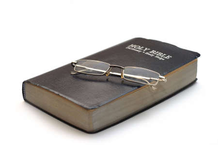 bible with folded reading glasses isolated on white photo