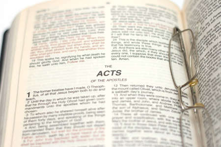 Open Bible with eyeglasses. Book of Acts photo