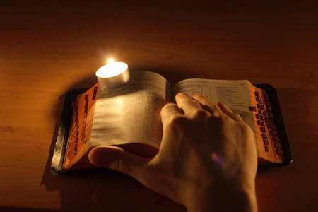 Hand, Bible and candle