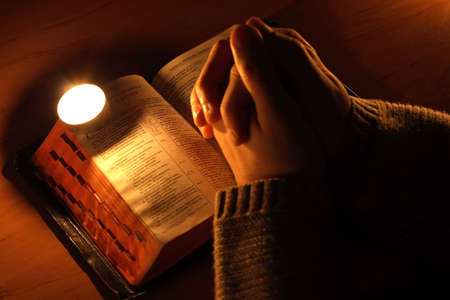 gospels: arms crossed in prayer on the Bible. Stock Photo