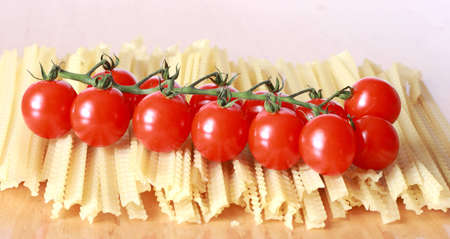 pasta and tomatoes on the background of the table Stock Photo - 10360523