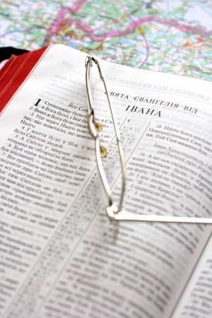 Bible in the Ukrainian language and glasses on map background photo