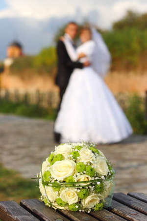 Bridal bouquet and the couple in the background photo