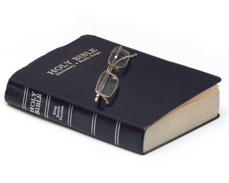 Holy Bible with eyeglasses isolated on white photo