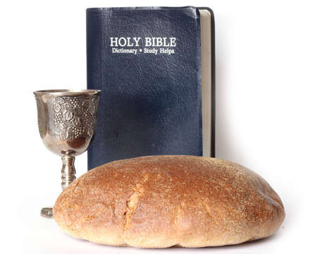 Holy Bible, cup and bread isolated on white background