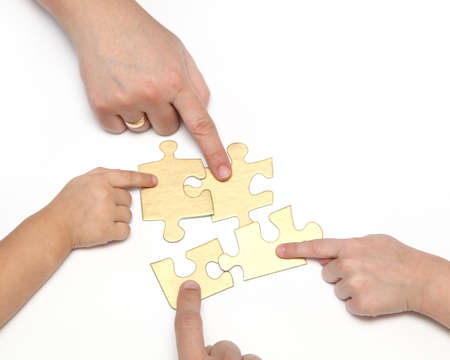 Cuatro manos con rompecabezas aislados en fondo blanco photo