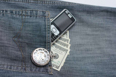 in a jeans pocket watch, phone and money photo