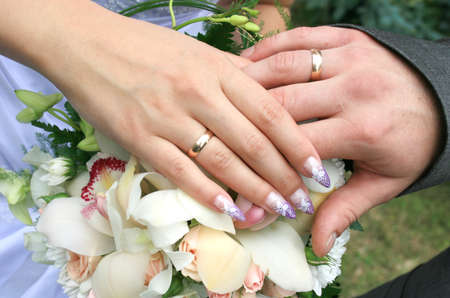 Hands newlyweds at the wedding bouquet photo