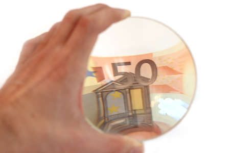 hand with the lens. considering the euro banknote photo