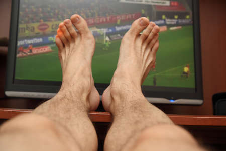 feet on the background of the TV showing football
