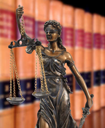 gerechtigheid: Een standbeeld van Themis op de achtergrond van de boeken van de wetten
