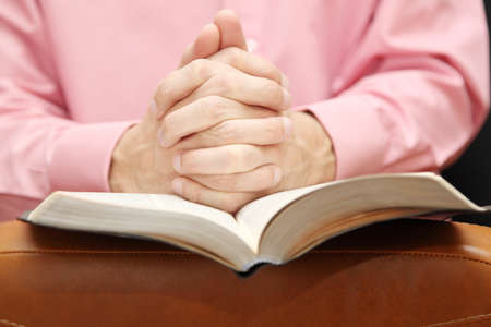 man folded his hands in prayer on the Bible Stock Photo