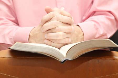 manos orando: hombre cruz� las manos en oraci�n en la Biblia