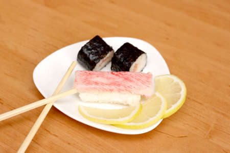 Fresh sushi with chopsticks on a white plate photo