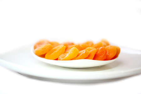 purgative: dried apricots in white plate isolated on white