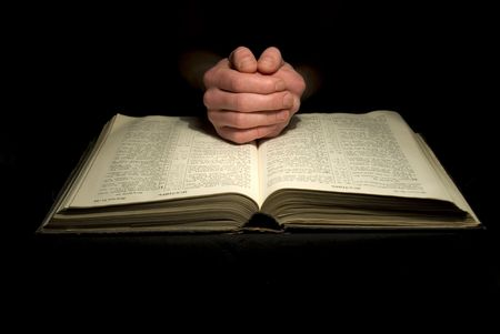 jesus praying: A mans hands clasped in prayer over a  Bible