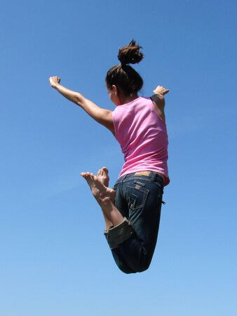 Young girl jump against a blue sky                                 photo
