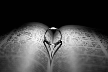 scripture: Wedding Ring and heart shaped shadow over a Bible