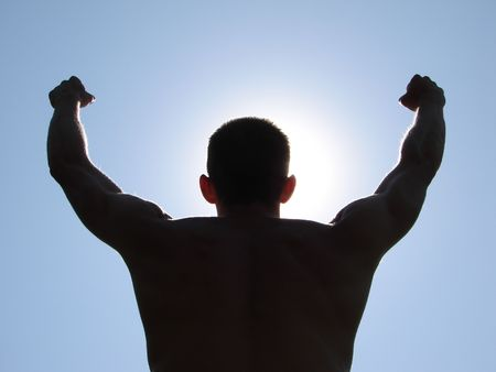 A man stands on against a sun with heaved up hands                                       photo