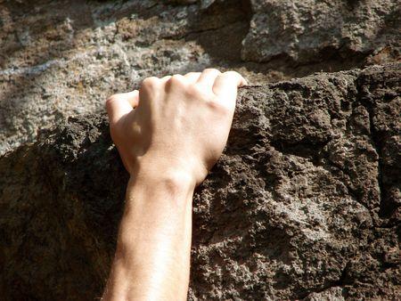 hand fixing on sandstone rock                                 Stock Photo