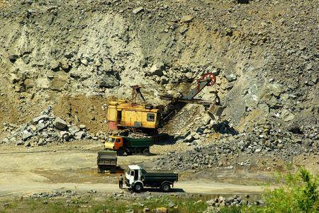 Ekskavator loads a stone on a truck     photo