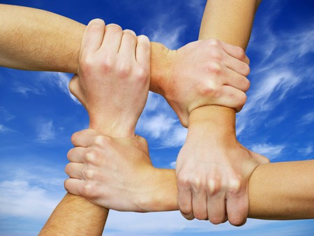 Linked hands on a white background symbolizing teamwork and friendship Stock Photo - 4408445