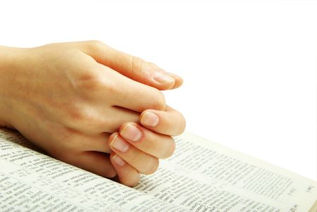hands clasped in prayer over a  Bible photo